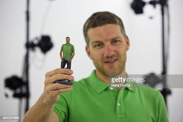 Martin Benes from 3D gang company holds printed figurine which looks like him on August 26 2014 in Prague Czech Republic The 3D scanner is the...