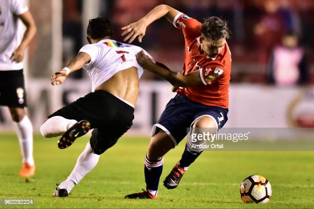 Martin Benitez of Independiente competes for the ball with Jose Reyes of Deportivo Lara during a match between Independiente and Deportivo Lara as...
