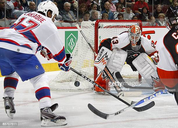 Martin Biron of the Philadelphia Flyers prepares to stop a shot from Georges Laraque of the Montreal Canadiens during their NHL game at the Bell...