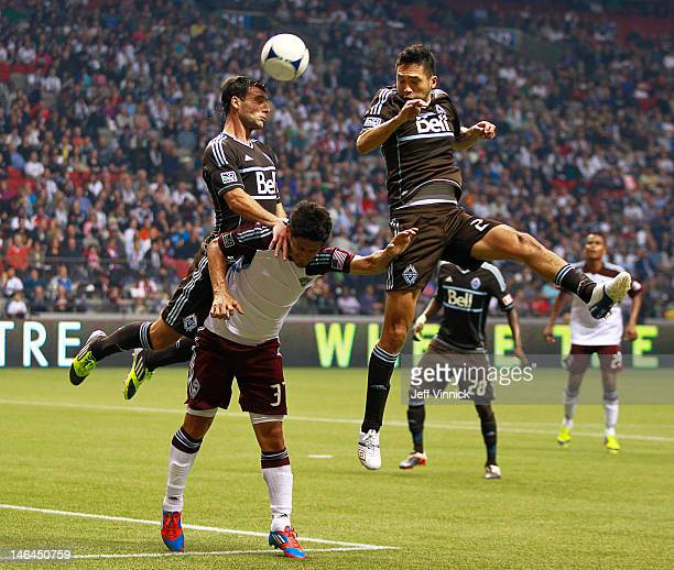 Martin Bonjour and Jun Marques Davidson of the Vancouver Whitecaps FC go high against Edu of the Colorado Rapids during their MLS game June 16 2012...