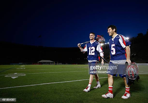 Martin Bowes and Jordan Burke of the Boston Cannons walk off of the field following their 14-6 win against the Charlotte Hounds at Harvard Stadium on...