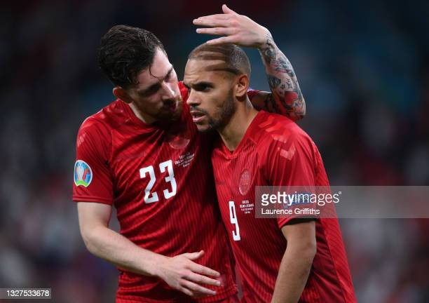 Martin Braithwaite of Denmark is consoled by Pierre-Emile Hojbjerg of Denmark following their side's defeat in the UEFA Euro 2020 Championship...