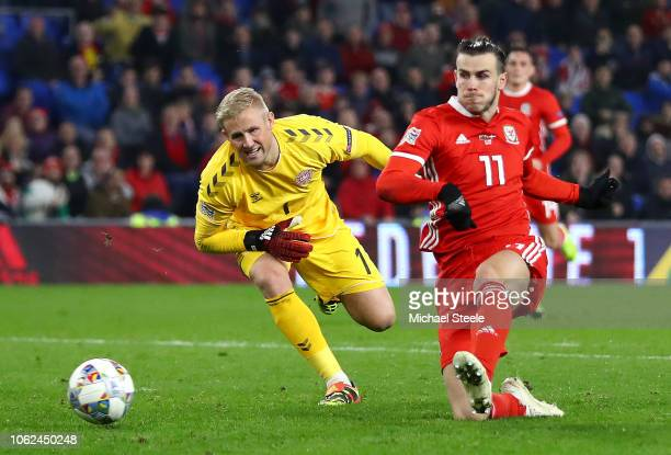 Martin Braithwaite of Denmark scores his team's first goal past Kasper Schmeichel of Denmark during the UEFA Nations League Group B match between...