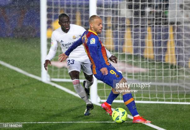 Martin Braithwaite of FC Barcelona is challenged by Ferland Mendy of Real Madrid during the La Liga Santander match between Real Madrid and FC...