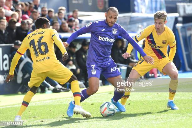 Martin Braithwaite of Leganes battles for possession with Moussa Wague of FC Barcelona and Frenkie de Jong of FC Barcelona during the La Liga match...