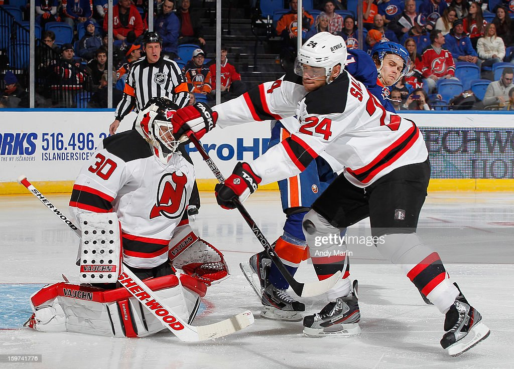 Martin Brodeur #30 of the New Jersey Devils eyes the puck as Bryce Salvador #24 tries to deflect it away against the New York Islanders during the Islanders home opener at the Nassau Coliseum on January 19, 2013 in Uniondale, New York.