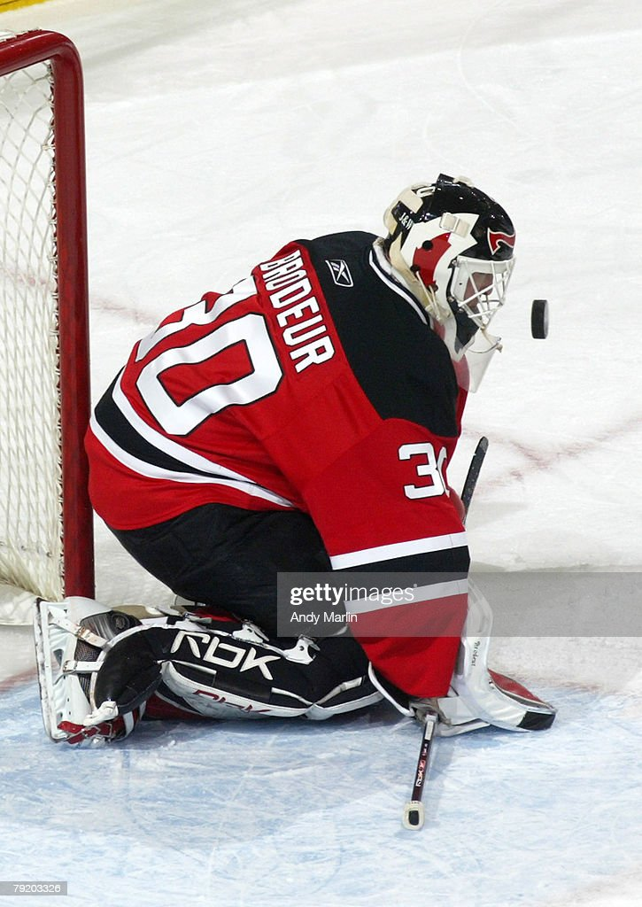 Martin Brodeur Of The New Jersey Devils Gets Hit In The Mask On A