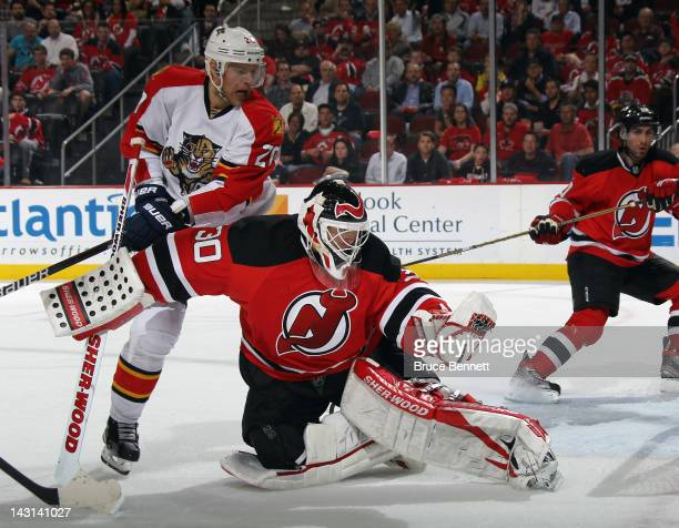 Martin Brodeur of the New Jersey Devils hangs on to the puck late in the third period as Sean Bergenheim of the Florida Panthers looks for a rebound...