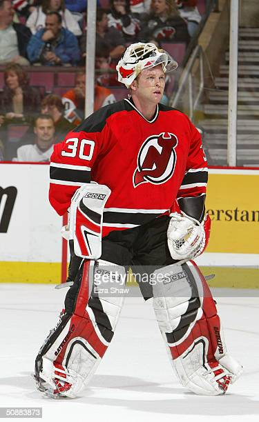 Martin Brodeur of the New Jersey Devils looks on with his mask flipped up during a break in game four of the Eastern Conference Quarterfinals against...