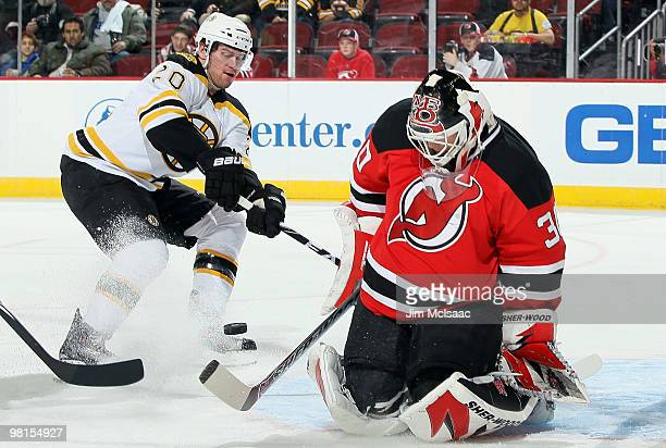 Martin Brodeur of the New Jersey Devils makes a first period save as Daniel Paille of the Boston Bruins looks for a rebound at the Prudential Center...