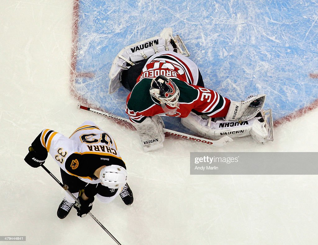 Martin Brodeur #30 of the New Jersey Devils makes a glove save as Zdeno Chara #33 of the Boston Bruins looks for a rebound during the game at the Prudential Center on March 18, 2014 in Newark, New Jersey.