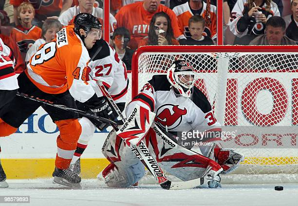 Martin Brodeur of the New Jersey Devils makes a save as Danny Briere of the Philadelphia Flyers reaches for the rebound in Game Four of the Eastern...