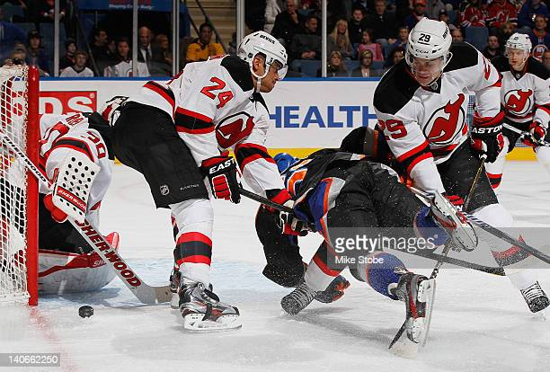 Martin Brodeur of the New Jersey Devils makes a save as his teammates Bryce Salvador and Mark Fayne check a New York Islanders player at Nassau...