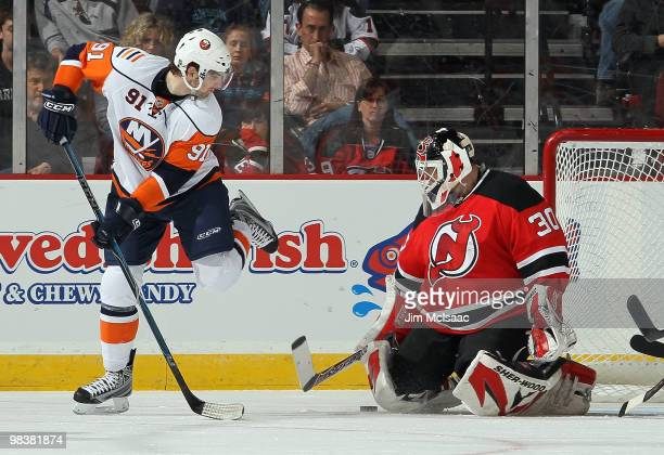 Martin Brodeur of the New Jersey Devils makes a save as John Tavares of the New York Islanders looks for the rebound at the Prudential Center on...