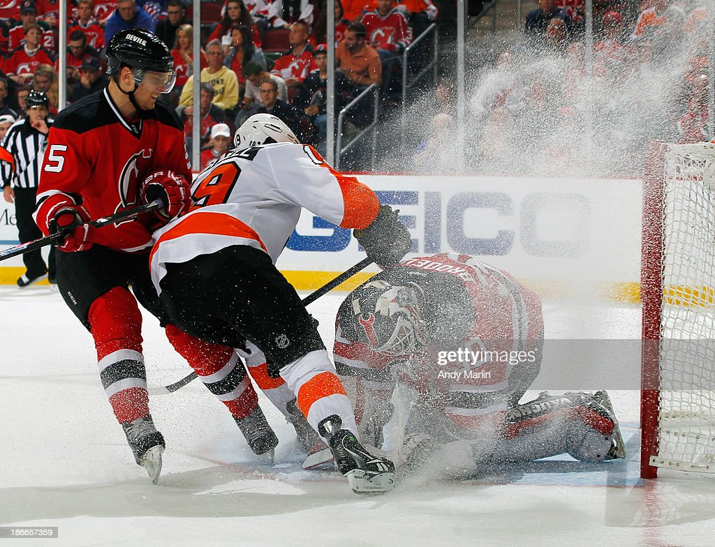 Martin Brodeur #30 of the New Jersey Devils makes a save while receiving a snow shower from Scott Hartnell #19 of the Philadelphia Flyers as Adam Larsson #5 defends during the game at the Prudential Center on November 2, 2013 in Newark, New Jersey.