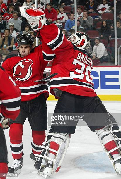 Martin Brodeur of the New Jersey Devils reaches over his teammate Mike Mottau to make a glove save against the Floride Panthers during their game at...