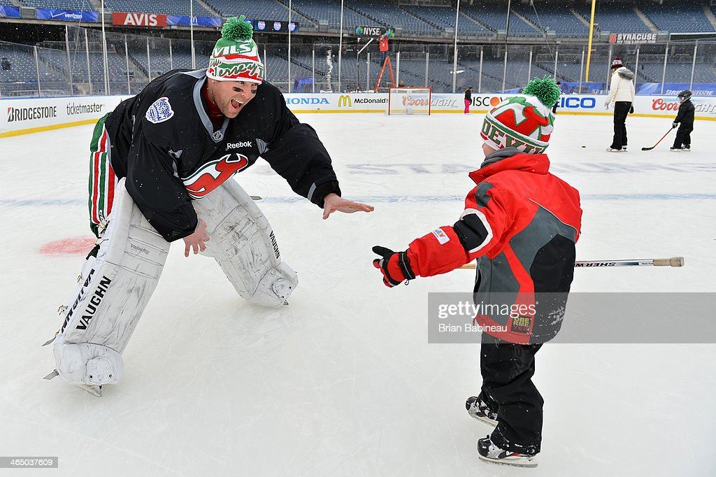 Martin Brodeur #30 of the New Jersey Devils skates with his son Maxime during the 2014 NHL Stadium Series practice sessions and family skate at Yankee Stadium on January 25, 2014 in New York City.