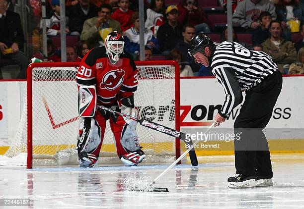 Martin Brodeur of the New Jersey Devils watches linesman Pat Dapuzzo clean the ice during the Devils game against the Carolina Hurricanes on November...