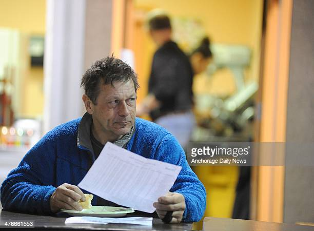 Martin Buser has breakfast and checks the race standings in the school cafeteria at the Nikolai checkpoint during the 2014 Iditarod Trail Sled Dog...