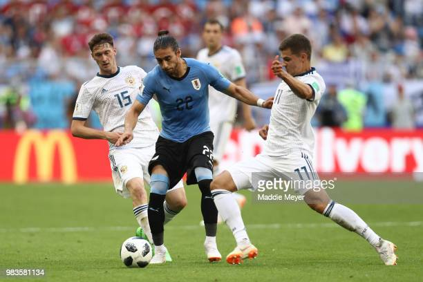 Martin Caceres of Uruguay challenge for the ball with Roman Zobnin and Alexey Miranchuk of Russia during the 2018 FIFA World Cup Russia group A match...