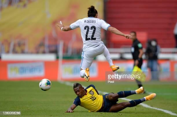 Martin Caceres of Uruguay jumps over Pervis Estupiñan of Ecuador during a match between Ecuador and Uruguay as part of South American Qualifiers for...