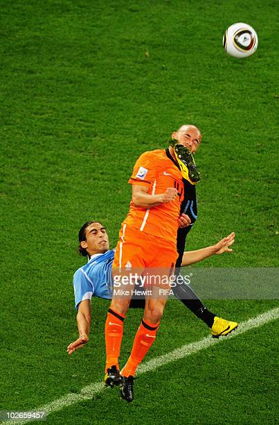 Martin Caceres of Uruguay kicks Demy De Zeeuw of the Netherlands during the 2010 FIFA World Cup South Africa Semi Final match between Uruguay and the...