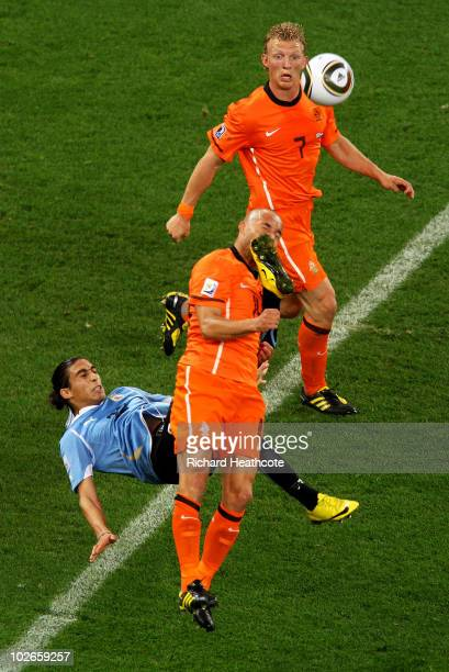 Martin Caceres of Uruguay makes a hard challenge on Demy De Zeeuw of the Netherlands, for which he receives a yellow card, during the 2010 FIFA World...