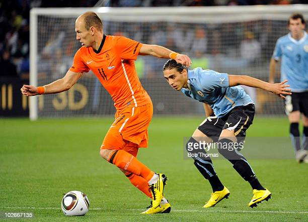 Martin Caceres of Uruguay watches Arjen Robben of the Netherlands during the 2010 FIFA World Cup South Africa Semi Final match between Uruguay and...