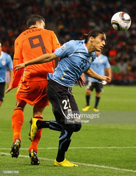 Martin Caceres of Uruguay wins the ball ahead of Robin Van Persie of the Netherlands during the 2010 FIFA World Cup South Africa Semi Final match...