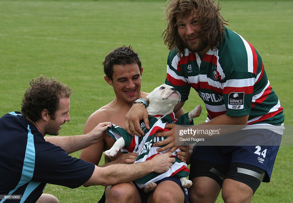 Martin Castrogiovanni (R) helps put a Leicester Tigers shirt on his bulldog puggy Fatty with the help of team mates Geordan Murphy (L) and Harry Ellis at Oadby Oval on August 25, 2009 in Leicester, England.