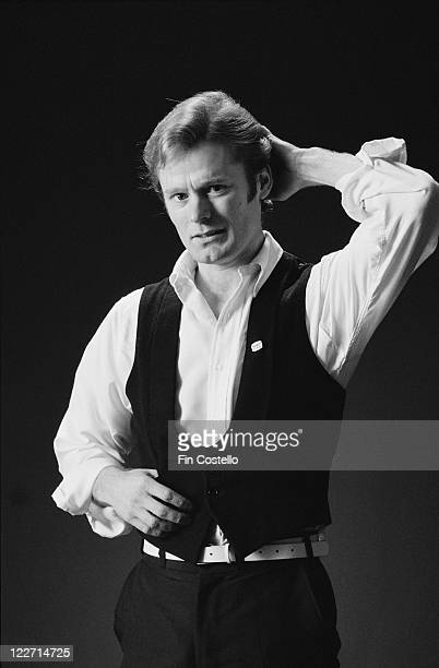 Martin Chambers, drummer with British rock band, The Pretenders, wearing a black wasitcoat and a white shirt as he poses for a studio portrait,...