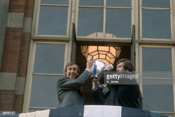 Martin Chivers and Pat Jennings of Tottenham Hotspur lift the League Cup trophy on the balcony of Tottenham Civic Centre North London following their...