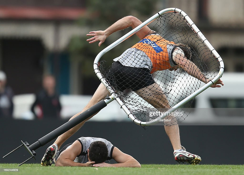 Martin Clarke (bottom) and Alan Toovey of the Magpies both accidentally collide with a training net during a Collingwood Magpies AFL training session at Gosch's Paddock on March 22, 2013 in Melbourne, Australia.