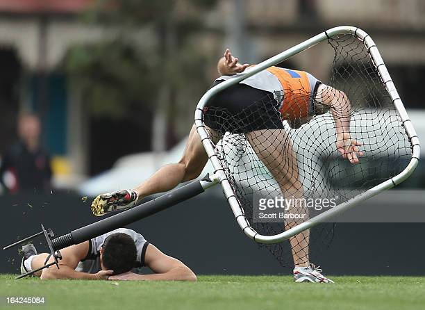 Martin Clarke and Alan Toovey of the Magpies both accidentally collide with a training net during a Collingwood Magpies AFL training session at...
