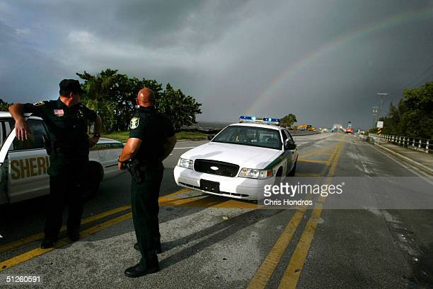 Martin County Sheriffs officers Roy Banks and Todd Lamn stand watch at a bridge to the barrier islands as a rainbow shines in the background...