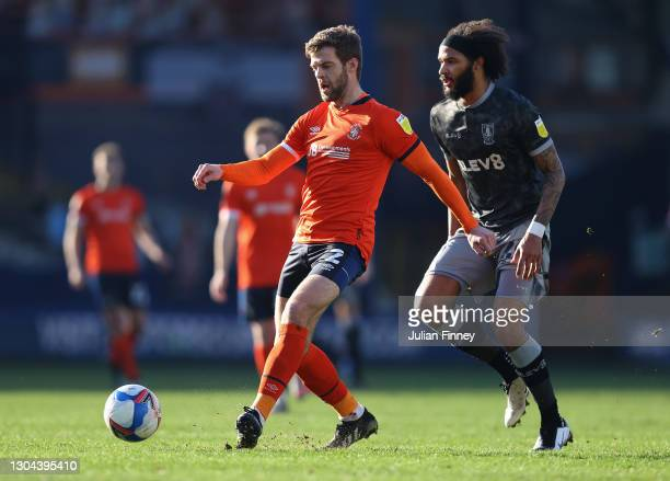 Martin Cranie of Luton Town is challenged by Isaiah Brown of Sheffield Wednesday during the Sky Bet Championship match between Luton Town and...