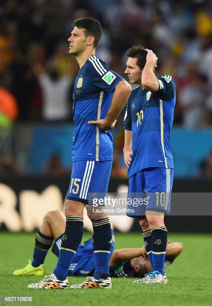 Martin Demichelis and Lionel Messi of Argentina look on after being defeated by Germany 10 in extra time during the 2014 FIFA World Cup Brazil Final...