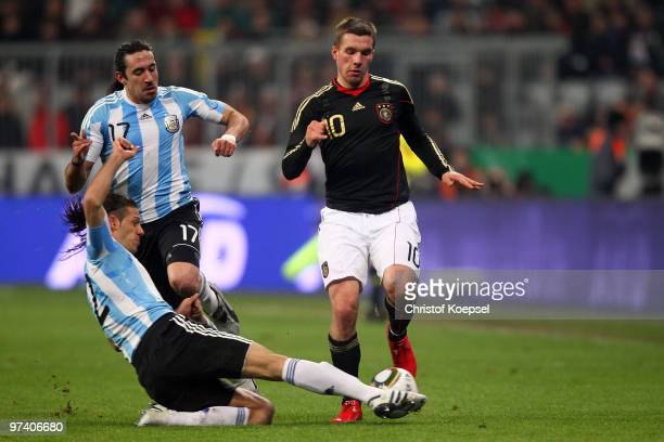 Martin Demichelis of Argentina challenges Lukas Podolski of Germany during the International Friendly match between Germany and Argentina at the...