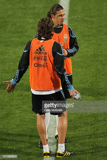 Martin Demichelis of Argentina's national soccer team spits water while talking to team mate Gabriel Heinze during a team training session on June 3...