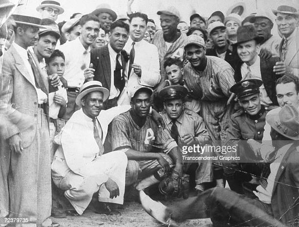Martin Dihigo, center kneeling, pitcher and outfielder for Almendares Baseball Club posese with fans and teammates after a game in 1930 in Havana.