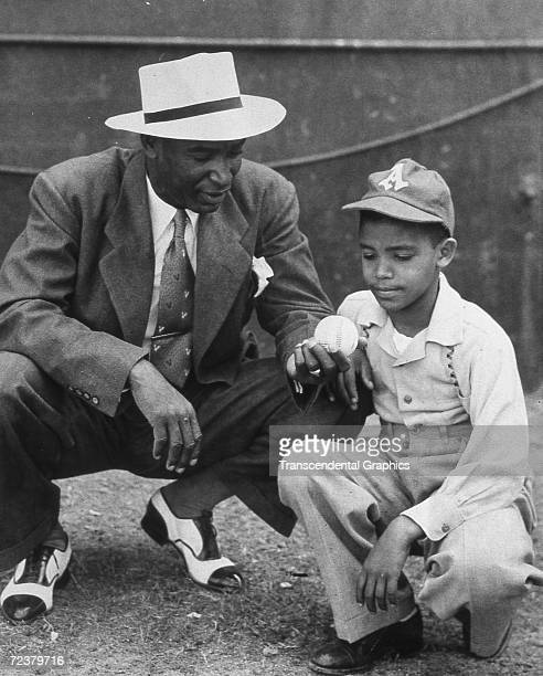 Martin Dihigo, kneeling with a young Almendares fan, discusses pitching in this 1942 meeting in Havana.