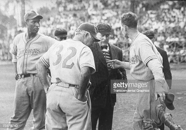 Martin Dihigo, manager of the Cienfuegos Baseball Club, left, argues with Adolfo Luque, manager of Habana, number 32, and the umpire during a gameat...