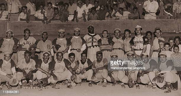 Martin Dihigo stands in the back row, center, in the uniform of an industrial league team, Union Laguna, while posing with an all-star team from a...