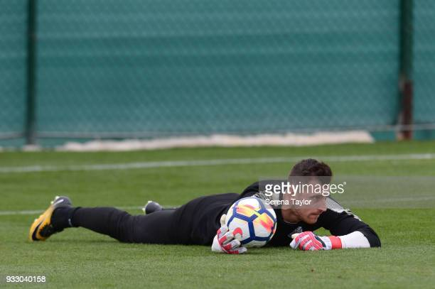 Martin Dubravka lays on the grass whilst he holds the ball during the Newcastle United Training Session at Hotel La Finca on March 17 in Alicante...