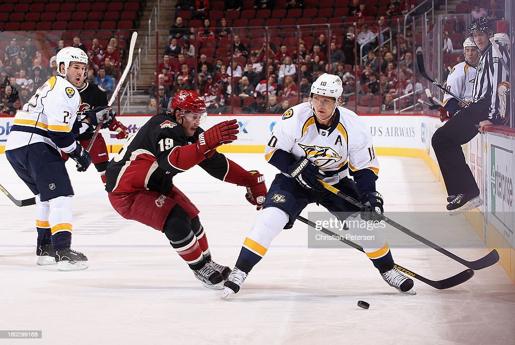 Martin Erat #10 of the Nashville Predators skates with the puck under pressure from Shane Doan #19 of the Phoenix Coyotes during the first period of the NHL game at Jobing.com Arena on January 28, 2013 in Glendale, Arizona.