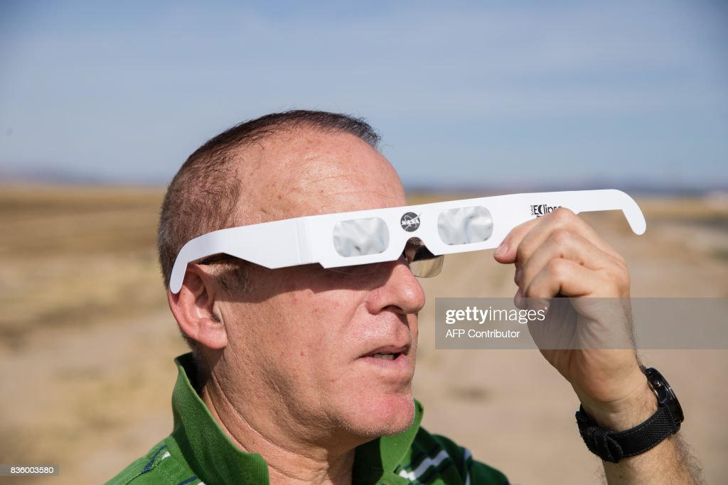 Martin Ferreira, a total eclipse enthusiast, tries out protective eye wear while waiting out standstill traffic on the side of a rural farm road near Madras, Oregon, August 20, 2017. /