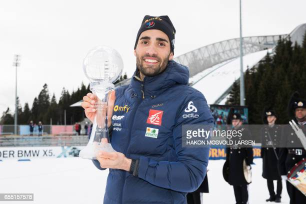 Martin Fourcade from France poses for photographers with the trophy for overall victory after he won the IBU Biathlon World Cup, Men 15 km Mass Start...