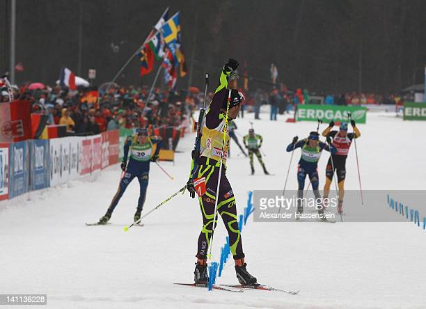 Martin Fourcade of France celebrates at the finish line winning the Men's 15km Mass Start ahead of Bjoern Ferry of Sweden and his team mate Frederik...