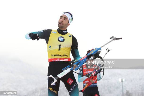 Martin Fourcade of France celebrates at the last shooting as hes team mate Quentin Fillon Maillet arrives at the shooting range during the Men 125 km...