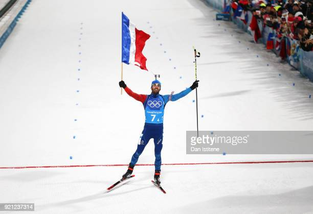 Martin Fourcade of France celebrates crossing the finish line to win the gold medal during the Biathlon 2x6km Women 2x75km Men Mixed Relay on day 11...